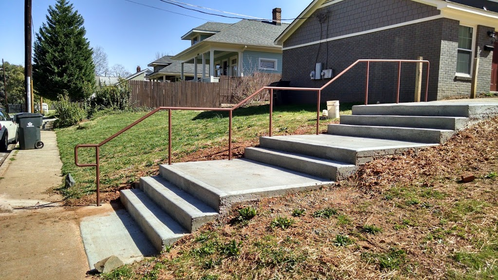 Double line ADA steel stair railings installed on concrete steps and landing