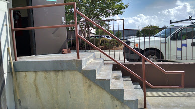 Single line ADA steel railings shown installed. Comforms to the landing stair conture of the concrete stairway