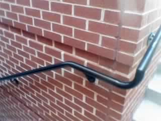 stair griprail attached to brick wall.